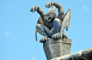 Gargoyle daemon sit on a roof of a building.